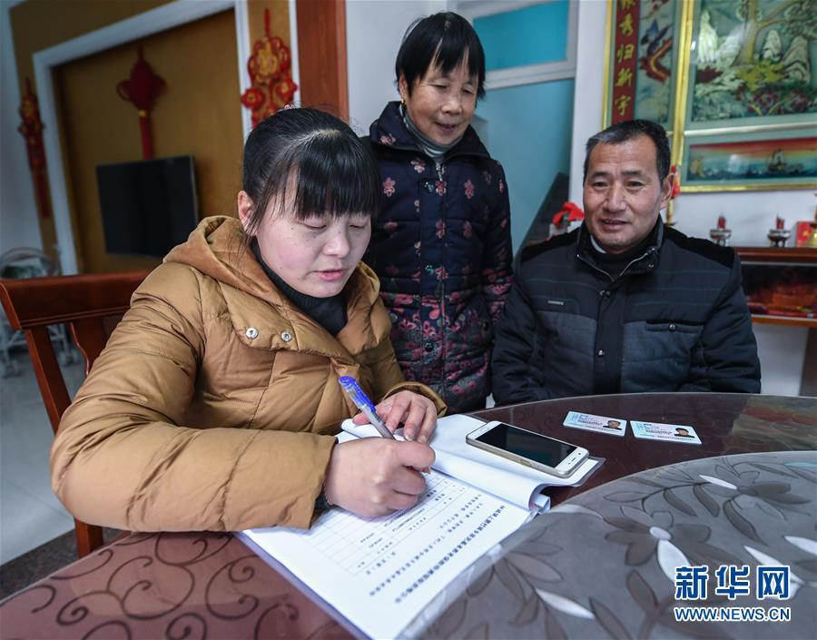 12月31日,林城镇上狮村村级代办员毕利锋(左一)正在为预约益的村民办理基本养老保险待遇核定、农民失地保险等营业。