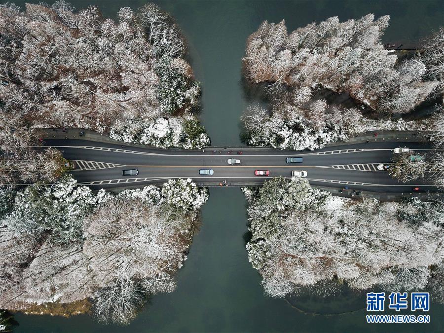 12月31日,汽车走驶在西湖景区杨公堤的一座桥上(无人机拍摄)。自12月30日首,浙江省大片面地区展现降雪,杭州市西湖景区银装素裹,表现稀奇的韵味,多多市民和游客纷纷来到湖边赏景。新华社记者 黄宗治