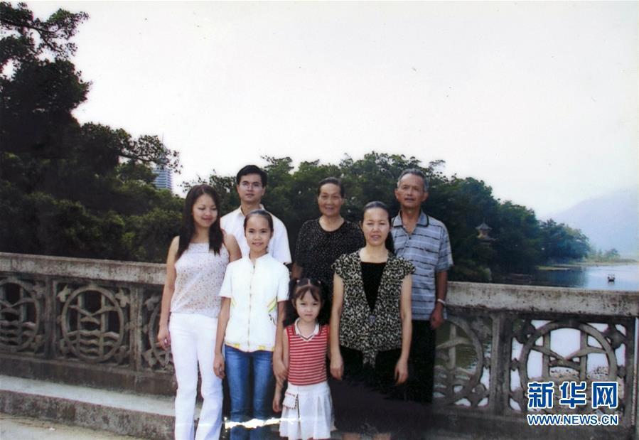2005年10月2日,在贵州省榕江县古州镇三宝侗寨,在黄万鑫(后排左一)和妻子(前排左一)结婚后的第二天,一家人拍摄全家福,在家替父母照望饲养的牛和猪的弟弟缺席了婚礼和这次相符影(2018年12月10日翻拍)。新华社发(黄万鑫)