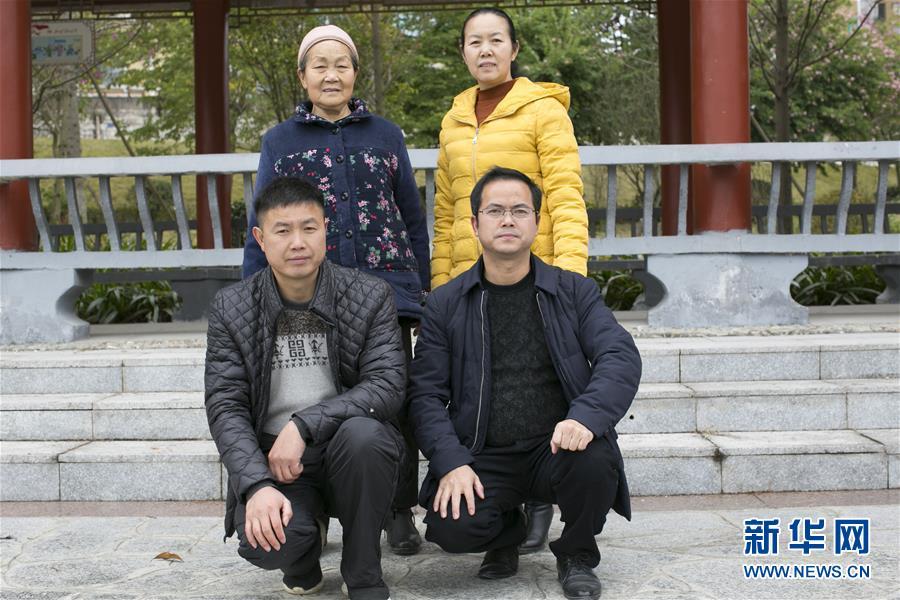 2018年12月9日,在贵州省榕江县古州镇百榕公园,黄万鑫(前排右一)和母亲、姐姐、弟弟听命1982年拍摄的第一张全家福的位置,一首相符影。 新华社发(罗运军)