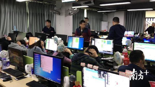 """记者随警现场跟拍,抓捕场面超波行!员工们双手抱头,每人桌上都有N台手机,电脑上还留着与""""客户""""疏导的界面。"""