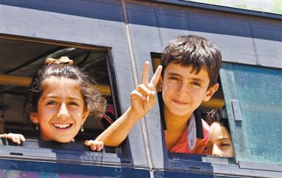 2018年以来,叙利亚的坦然局势逐渐趋稳,大批之前逃离战区的民多重返家园。图为在叙利亚德拉省布斯拉,两名儿童在重返家园的大巴车上做手势。