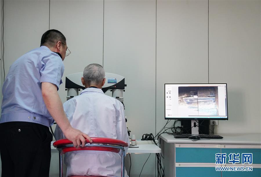 在黑龍江省公安廳刑事技術總隊實驗室中,崔道植(右)在進行痕跡檢驗工作(6月11日攝)。新華社記者王松攝