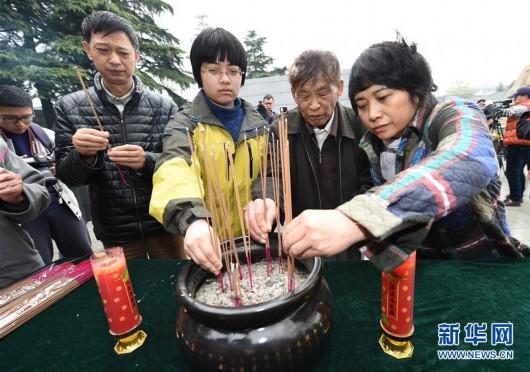 南京大屠杀幸存者常志强(右二)率亲属在侵华日军南京大屠杀遇难同胞纪念馆内的遇难者名单墙前焚香(2015年4月5日摄)。新华社记者孙参摄