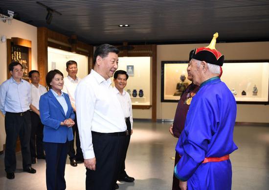 15日,习近平在赤峰博物馆同古典民族史诗《格萨(斯)尔》非物质文化遗产传承人亲切交谈。