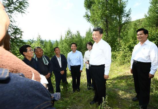 15日,习近平在赤峰市喀喇沁旗马鞍山林场同正在劳作的护林员们交流,了解他们的工作、生活、家庭情况。