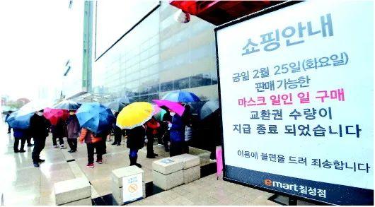 韩国大邱,居民在雨中列队购买口罩,超市告示每人当日限购一只口罩。来源:新华社